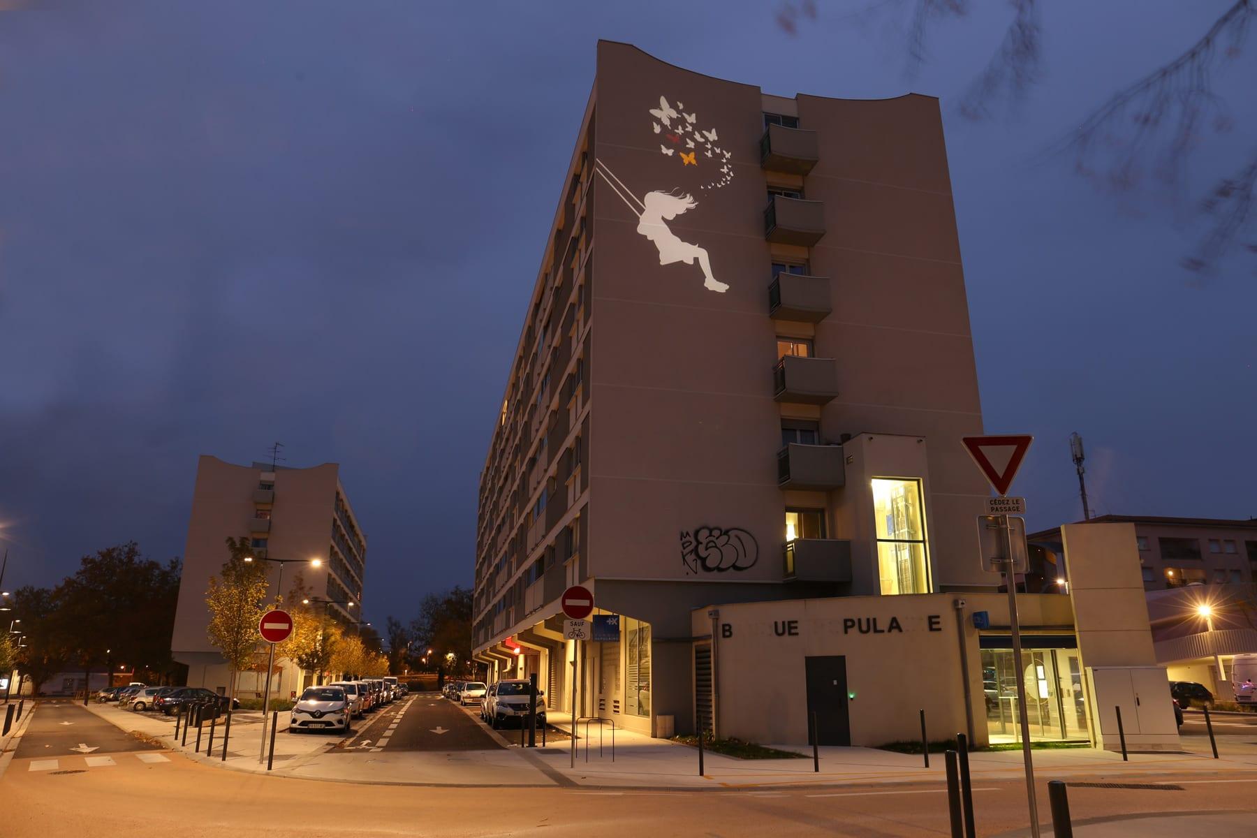 Vue d'une façade d'imeuble de nuit avec une projection d'image lumineuse